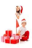 偷看从后面的圣诞老人帽子的愉快的小孩 免版税图库摄影