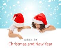 偷看从后面的圣诞老人帽子的愉快的小孩 免版税库存照片