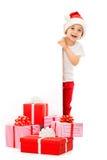 偷看从后面的圣诞老人帽子的愉快的小男孩 免版税图库摄影