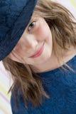 偷看从他的帽子下面的八岁的女孩 免版税库存照片