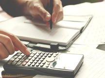 储款、财务、经济和家庭概念-接近有计数的计算器的人在家做笔记 免版税库存图片