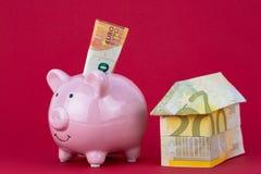 储款和投资-存钱罐,莓颜色背景的金钱房子 免版税库存图片