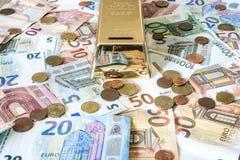 储款现金金钱概念欧洲钞票在书桌存钱罐金型钢救球的所有大小和分硬币 免版税库存图片