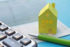 储蓄帐户存款簿、计算器、笔和黄色纸房子蓝色背景的 库存图片