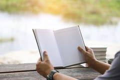 储蓄照片:供以人员读书和写笔记在木tabl 免版税库存照片