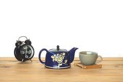 储蓄照片:在木桌和白色墙壁上的蓝色茶罐有vi的 免版税库存照片