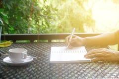 储蓄照片:有写笔记本的特写镜头人的咖啡杯  免版税库存图片