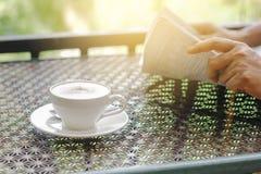 储蓄照片:热奶咖啡在一张桌上的咖啡杯有背景o 库存照片