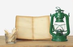 储蓄照片:笔记本和灯笼装饰在木背景 库存照片