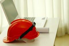 储蓄照片-橙色安全帽和norebook在白色桌上 免版税库存照片