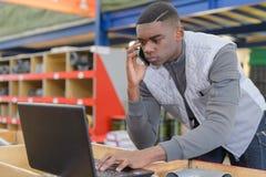 储藏使用电话和膝上型计算机的经理在大仓库 库存照片