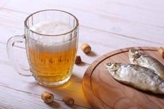储藏啤酒杯子和快餐在白色木桌上 免版税库存图片