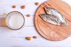 储藏啤酒杯子和快餐在白色木桌上 免版税库存照片
