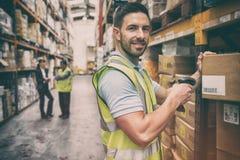 储藏工作者扫描箱子,当微笑对照相机时 免版税库存照片