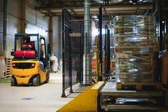 储藏总之衣裳的雇员,司机Reachtruck繁忙研究继续前进装载者板台的后勤学 在manuf的人劳方 库存照片