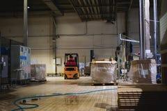 储藏总之衣裳的雇员,司机Reachtruck繁忙研究继续前进装载者板台的后勤学 在manuf的人劳方 免版税库存照片