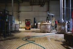 储藏总之衣裳的雇员,司机Reachtruck繁忙研究继续前进装载者板台的后勤学 在manuf的人劳方 库存图片
