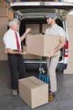 储藏经理和交付司机谈话在搬运车旁边 免版税库存照片