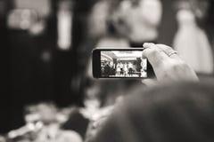 傲德萨,乌克兰- 2015年5月30日:妇女手有人智能手机的录音录影在毕业晚会的阶段 免版税库存照片