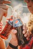 傲德萨,乌克兰- 2014年10月15日:关闭户外喝从玻璃瓶的愉快的年轻夫妇冷的百事可乐与 库存照片