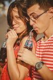 傲德萨,乌克兰- 2014年10月15日:关闭户外喝从玻璃的年轻愉快的少年夫妇冷的百事可乐 免版税库存照片