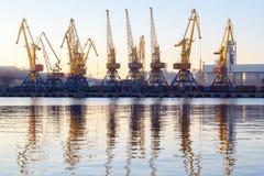 傲德萨,乌克兰- Januadry 02日2017年:容器起重机在货物口岸终端,货物起重机在水中反射了 日落 库存图片
