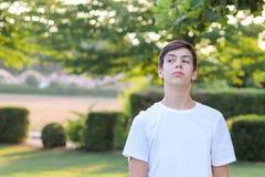 傲慢地看和触犯某人的白色衬衣的少年男孩 图库摄影