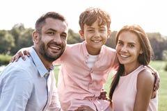 傻瓜 走在象草的领域儿子的三口之家拥抱同水准 库存照片