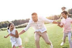 傻瓜 跑在象草的领域的四口之家演奏使用 免版税库存照片
