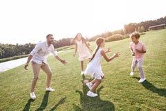 傻瓜 跑在象草的领域的四口之家演奏使用 免版税库存图片