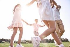 傻瓜 跳舞在gra的圈子的四口之家举行的手 免版税图库摄影