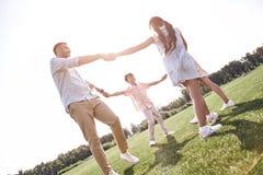 傻瓜 跳舞在gra的圈子的四口之家举行的手 库存照片