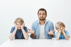 儿子为什么是疯狂的 是无知的紧张的公公画象坐与两个逗人喜爱的男孩在桌上,耸肩和 图库摄影