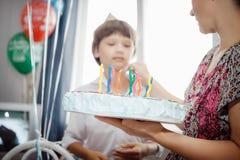 儿子厨师的母亲与蜡烛的一个蛋糕 免版税库存照片