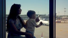 儿子和母亲在看对飞机的机场坐 股票录像