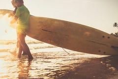 儿子和父亲冲浪者在与委员会的海浪走 免版税库存图片