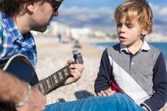 儿子和父亲在海滩的唱歌歌曲 免版税图库摄影