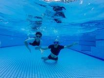 儿子和爸爸在水池,爸爸游泳在水面下教他的儿子潜水在水下 免版税图库摄影