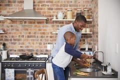 儿子帮助的父亲菜为膳食做准备在厨房里 免版税图库摄影