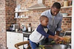 儿子帮助的父亲菜为膳食做准备在厨房里 免版税库存照片