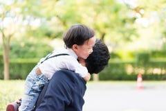 儿子拥抱他的父亲和微笑与偶然衣服在公园 免版税库存图片