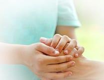 儿子握她的母亲的手 免版税库存照片