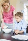 儿子的母亲倾吐的牛奶在桌上 免版税库存照片