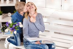儿子祝贺他心爱的母亲并且给她郁金香花束  庆祝,妇女的天的概念 日母亲s 图库摄影