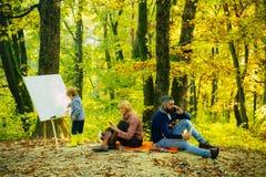 儿子绘画图片本质上 ( E E 妈妈和爸爸工作公园 库存图片