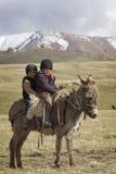 儿子KUL湖,吉尔吉斯斯坦- 6月10 乘坐donke的两个孩子 免版税图库摄影