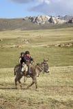 儿子KUL湖,吉尔吉斯斯坦- 6月10 乘坐donke的两个孩子 免版税库存图片
