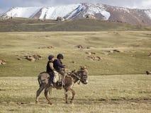 儿子KUL湖,吉尔吉斯斯坦- 6月10 乘坐donke的两个孩子 免版税库存照片