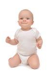 婴儿小小孩坐她膝盖和愉快微笑 免版税库存照片