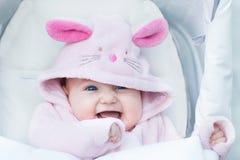 婴儿推车的可爱的女婴在兔宝宝雪衣服 图库摄影